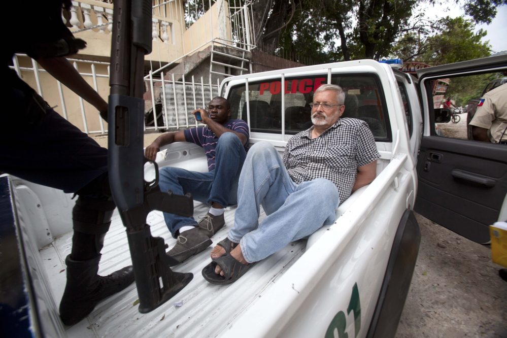 U.S. citizen Michael Geilenfeld waits in handcuffs alongside his orphanage manager after Haitian police arrested Geilenfeld on Sept. 5 near Port-au-Prince. Geilenfeld was charged with indecent assault involving alleged sexual abuse at St. Joseph's Home For Boys.