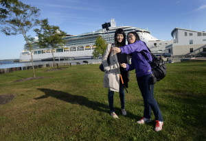 After touring the Portland area, Fionne Yip, left, and Mav Yip of Toronto take a selfie with the Brilliance of the Seas in the background just before reboarding the cruise ship Monday.