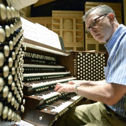 Cornils listens to the sounds of the Kotzschmar Organ while playing it at Merrill Auditorium.