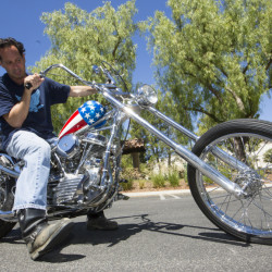 "Michael Eisenberg, sits on the customized Captain America chopper Peter Fonda rode in ""Easy Rider"" at the Profiles in History auction house in Calabasas, Calif.  Eisenberg, a California businessman who once co-owned a Los Angeles motorcycle-themed restaurant with Fonda and ""Easy Rider"" co-star Dennis Hopper, owns the motorcycle that has come to symbolize the counterculture of the 1960s."