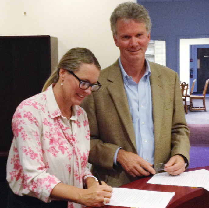 Heather Ashby, who bought 415 Congress St., signs papers Thursday with David Perkins, a lawyer for the building's former owner.
