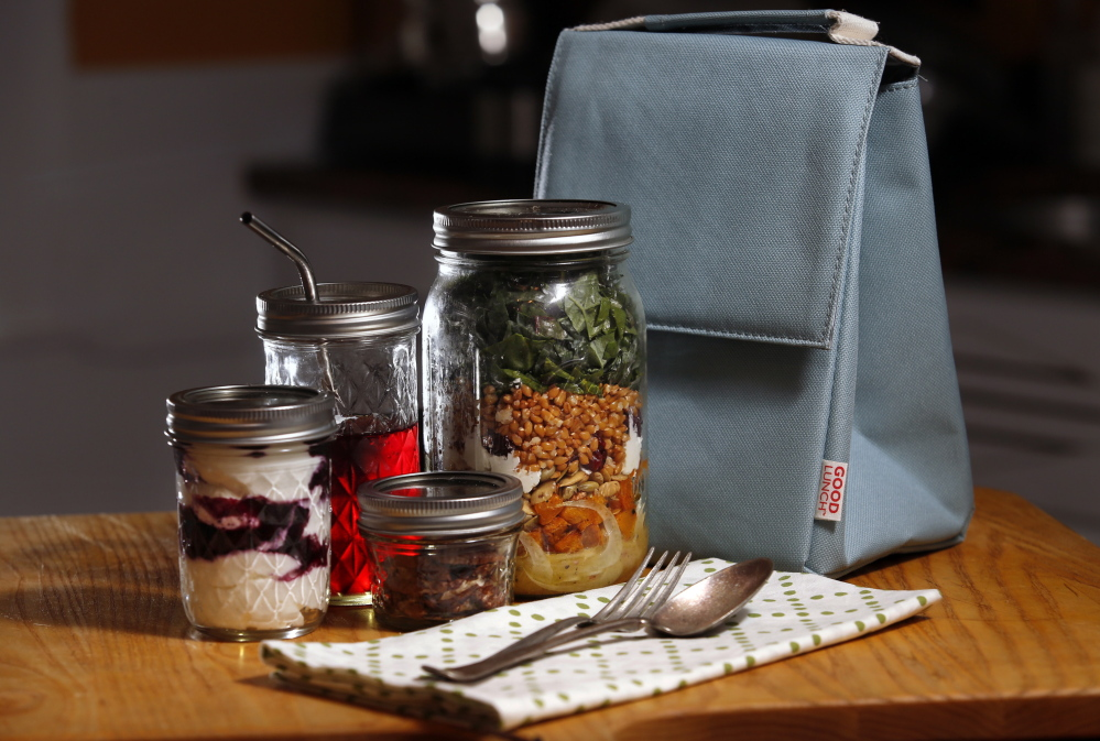 A lunch of salad, yogurt and other snacks, all packed in Mason jars, with a cloth napkin and real silverware means no plastic or paper waste.