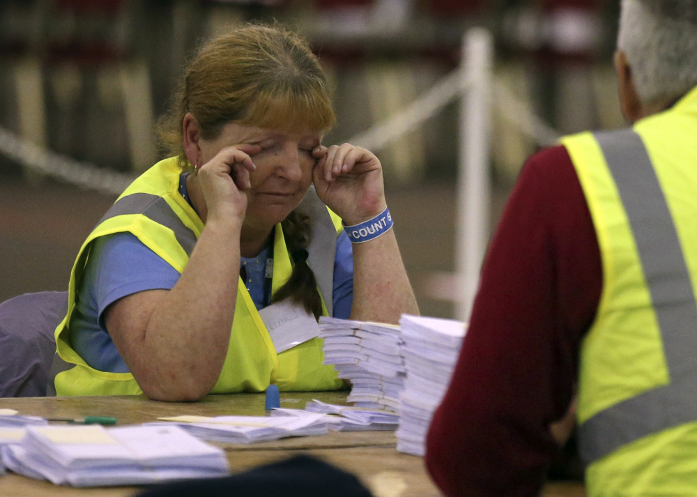 A vote counter in Edinburgh, Scotland, rubs her eyes as the staff counts ballot papers through the night in the Scottish Independence Referendum.