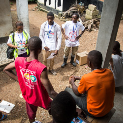 In this photo taken on Friday, Idrissa Kargbo, top right, Sierra Leone's national marathon champion, helps volunteers distribute information on Ebola in Freetown, Sierra Leone.