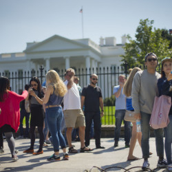 Tourist stop to take their photograph in front of the White House in Washington, Saturday.  The Secret Service is coming under renewed scrutiny after a man scaled the White House fence and made it all the way through the front door before he was apprehended.