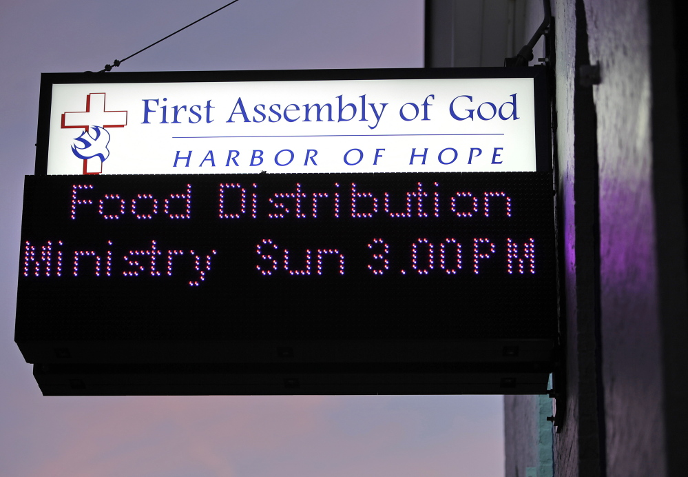 A sign at the First Assembly of God on Cumberland Avenue in Portland calls attention to the church's Food Distribution Ministry. Members of the small congregation give away up to 10,000 pounds of food each Sunday.