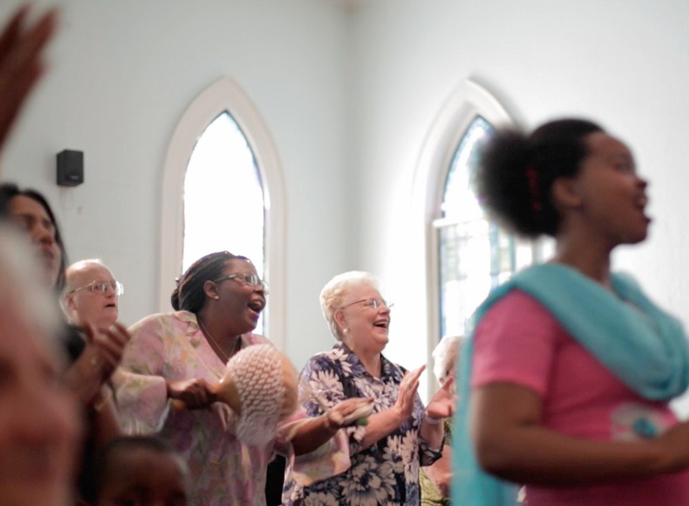 Angie Guillette, center, and fellow church members worship at the First Assembly of God church on Cumberland Avenue in Portland. Each week after the Sunday service, Guillette and others help distribute food to hundreds of families in the inner city neighborhood.