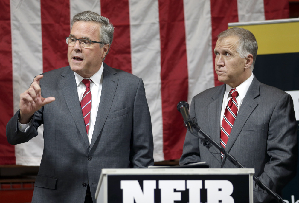 """Former Florida Gov. Jeb Bush, left, answers a question as North Carolina Republican Senate candidate Thom Tillis listens Wednesday during an event in support of Tillis in Greensboro, N.C. Such events give Bush a platform to speak about the country's ills and the prospect of a """"new American century."""""""