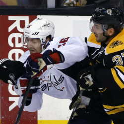 Washington right wing Eric Fehr, left, struggles for position with Boston center Patrice Bergeron, right, during the first period of the Bruins' 2-0 preseason victory Wednesday night at Boston.