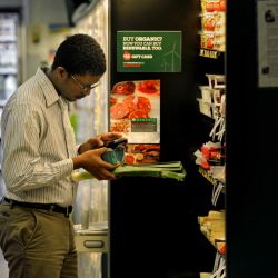 Weno Gaseitsiwe uses his smartphone at an organic store in Washington to check with his wife as he shops for cheese and other items to use in a dinner they're making for guests.
