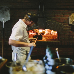 Joshua Doria prepares a wood-burning oven as dinner service starts at Fore Street Restaurant in Portland.