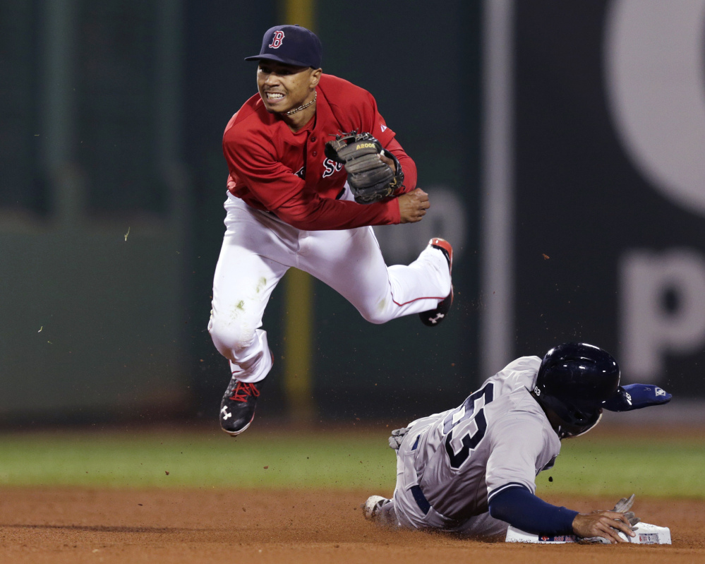 Red Sox second baseman Mookie Betts watches his throw to first after forcing out the Yankees' Antoan Richardson on a double play in the ninth inning Friday night at Fenway Park.