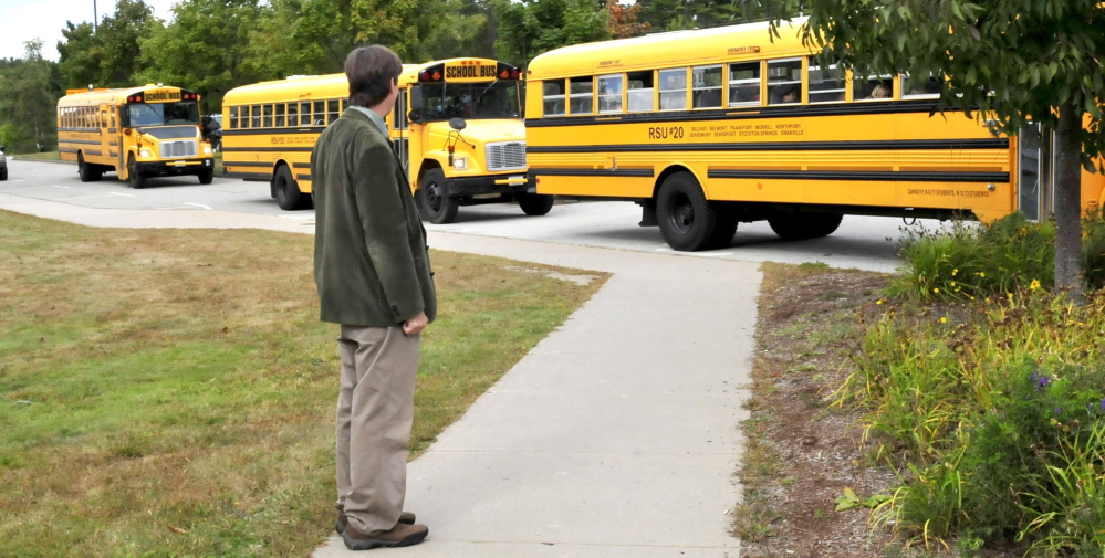 Kent Hoffman, principal of Searsport District High School, watches RSU 20 buses. The future of RSU 20 is uncertain.