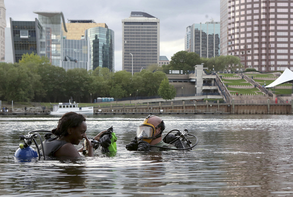 Nicole Green, left, of West Hartford, Conn., and her dive instructor Woodrow Tinsley clear their masks before diving in the Connecticut River, in East Hartford, Conn. Tinsley, an East Hartford police officer, is hoping to identify the ship that sunk in the 1970s.