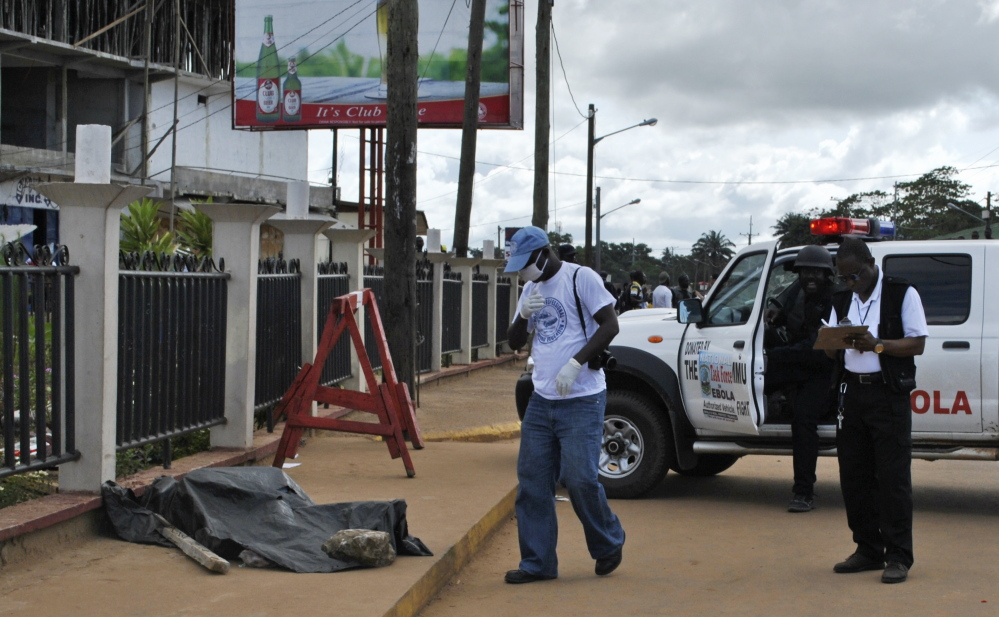 Police carry out forensic testing for the Ebola virus on a body found on a street in Monrovia, Liberia, on Saturday. Aid is arriving too late for thousands of victims of the deadly virus.