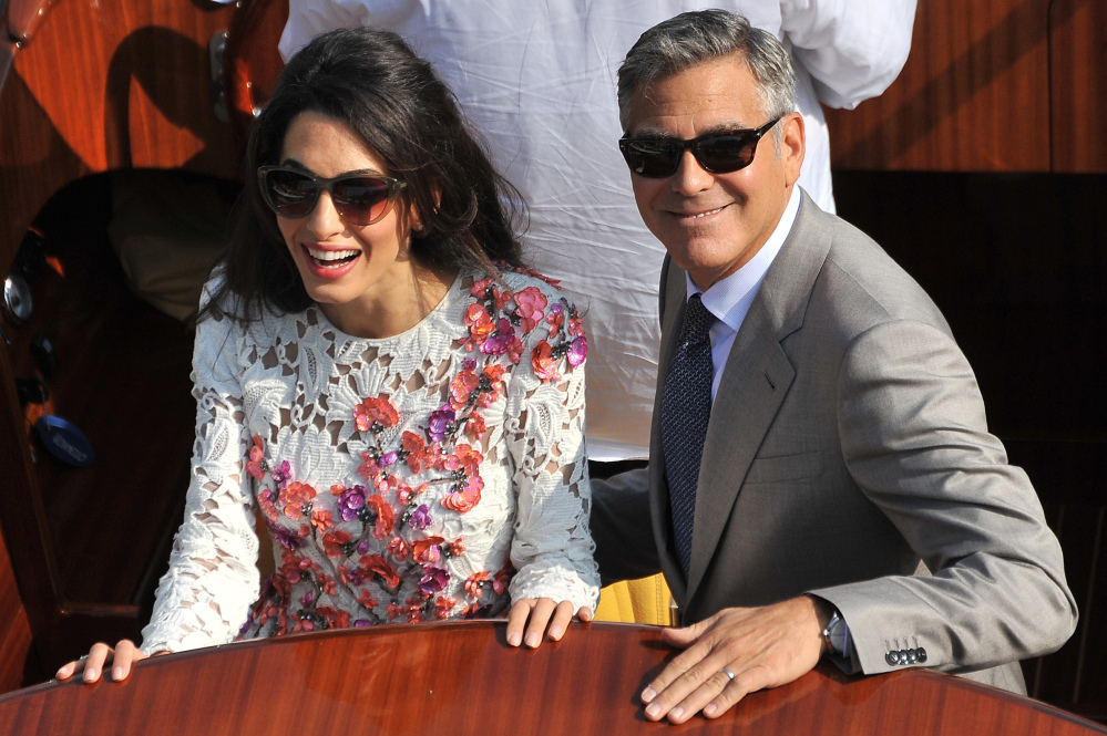 George Clooney, wearing his wedding ring, and his wife Amal Alamuddin, cruise the Grand Canal after leaving the Aman luxury Hotel in Venice, Italy, on Sunday.