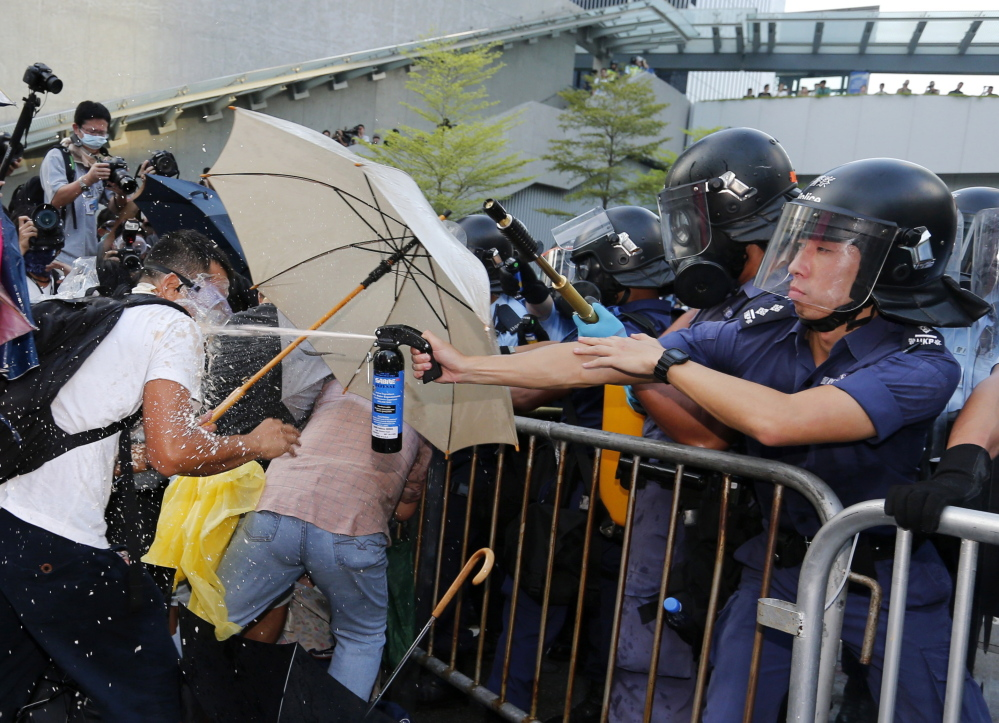 An anti-riot policeman, right, shoots pepper spray at a pro-democracy demonstrator outside the government headquarters in Hong Kong on Sunday.