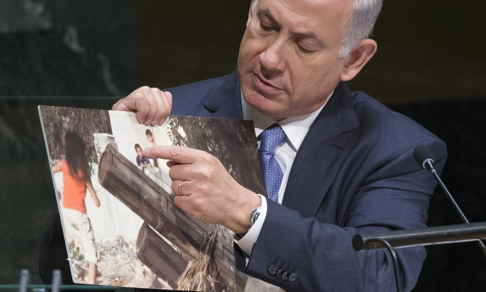 Israel's Prime Minister Benjamin Netanyahu points to a photo he says shows rocket launchers placed in residential neighborhoods of Gaza, as he addresses the 69th session of the United Nations General Assembly at U.N. headquarters Monday.