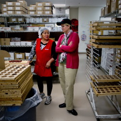 Hue Nguyen of Westbrook, a production associate at Haven's Candies, chats with new owner Erin Collins of Freeport while in the candy production area of the business in Westbrook on Tuesday.