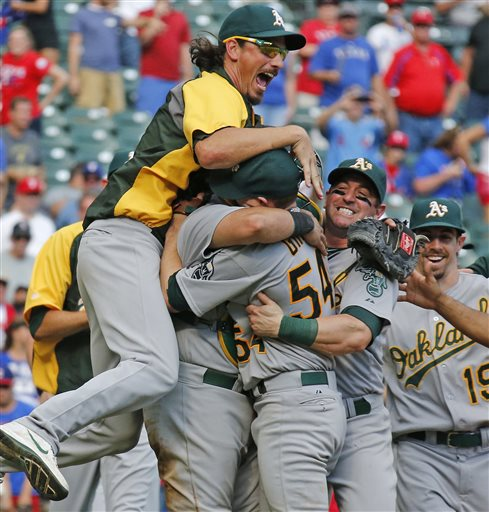 Oakland A's pitcher Jeff Samardzija, left, and other teammates embrace starting pitcher Sonny Gray after the final out in their wild card-clinching 4-0 win against the Texas Rangers in Arlington on Sunday. The Associated Press