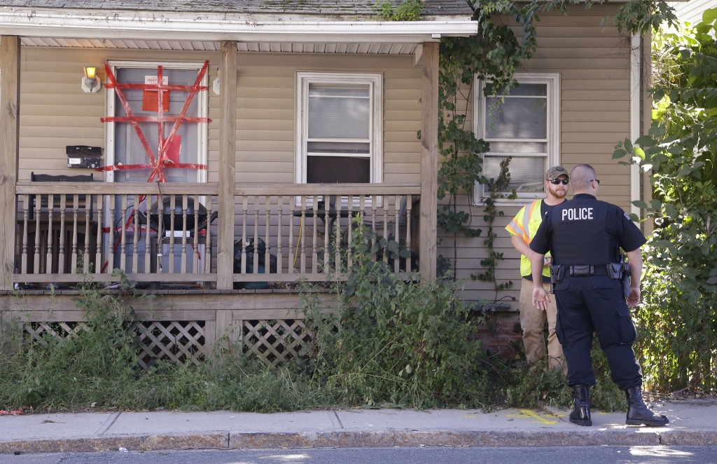 """A Blackstone police officer talks with a utility worker while standing post outside a house where a Massachusetts prosecutor said the bodies of three infants were found Thursday. Both """"condemned"""" and """"keep out"""" signs are attached behind police tape to the front door. The utility worker laid some paint markings on the street in front of the house."""