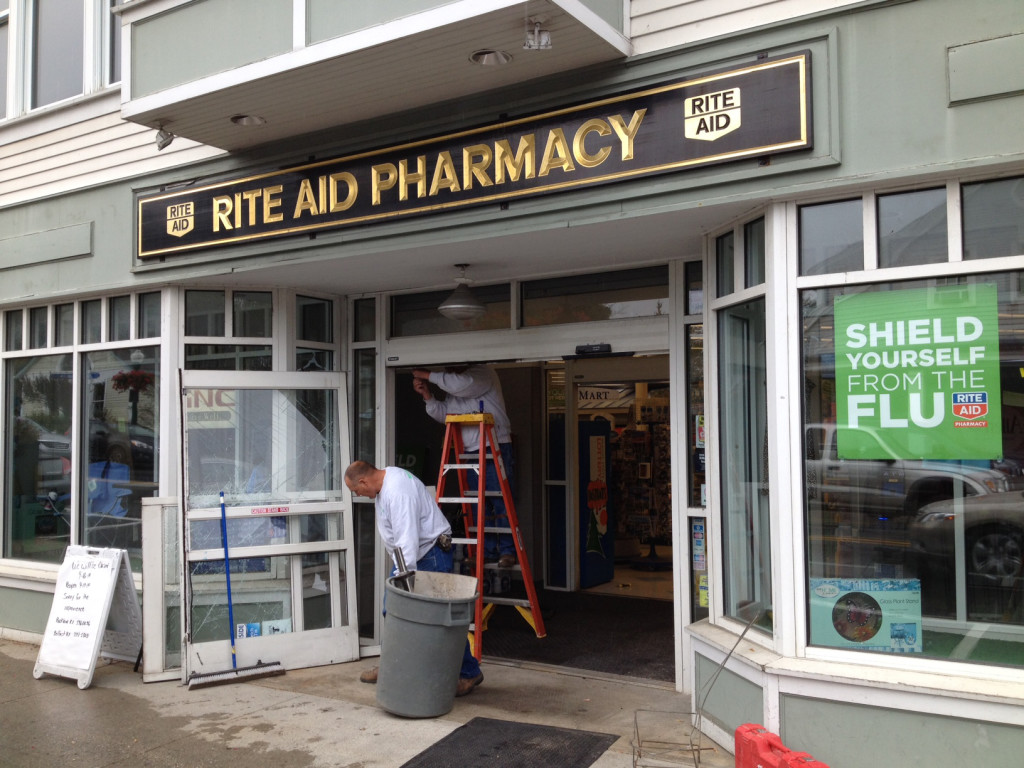 A worker replaces the front door of the Rite Aid pharmacy on Elm Street in Camden, following an overnight standoff that ended with the self-inflicted shooting death of a robbery suspect.