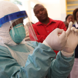 A woman wears protective clothing during a tour  of one of the Ebola Centers in Harare, Zimbabwe Tuesday. Although Zimbabwe has not reported any cases of the deadly virus wreaking havoc in West Africa, it is on high alert and has set up Ebola centers in order to screen people suspected of carrying virus. The Associated Press
