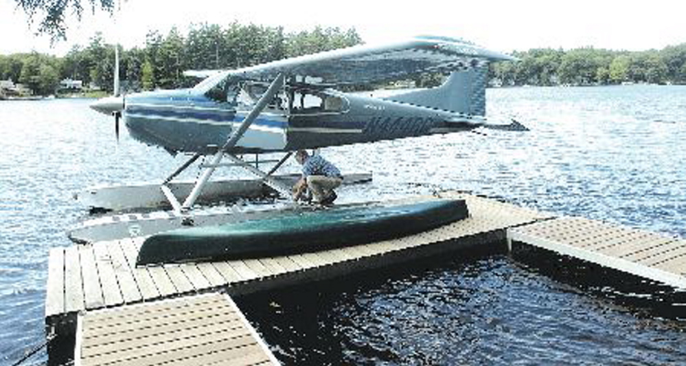 Bill McKay of Oakland secures his float plane to his dock on Messalonskee Lake in August 2006 after taking a short flight.