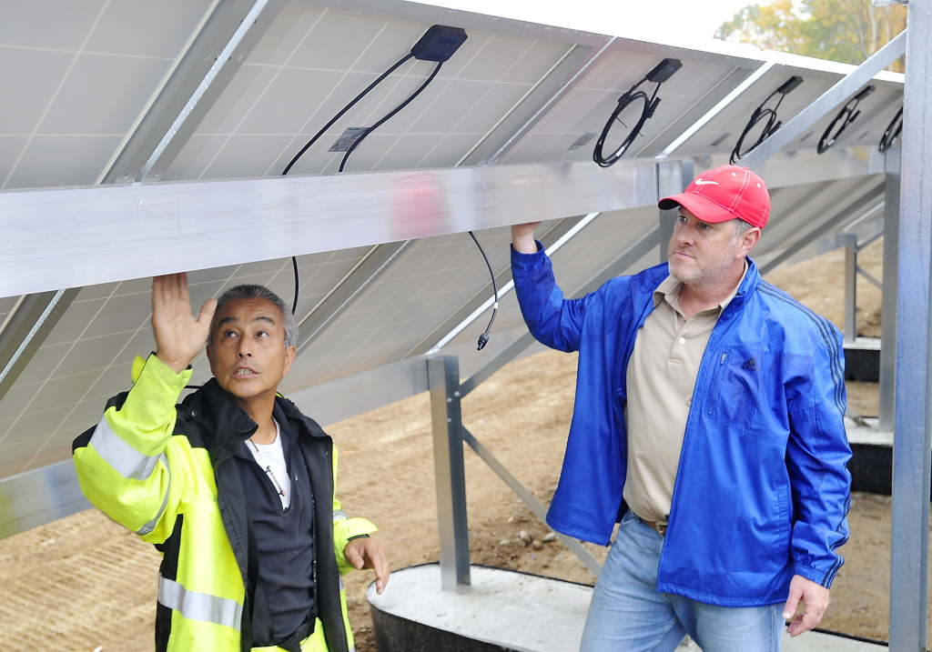 Naoto Inoue, left, president of Talmage Solar Engineering Inc., explains how the panels will be connected to each other and the inverters to Matt Hancock, co-owner of Mount Abram.