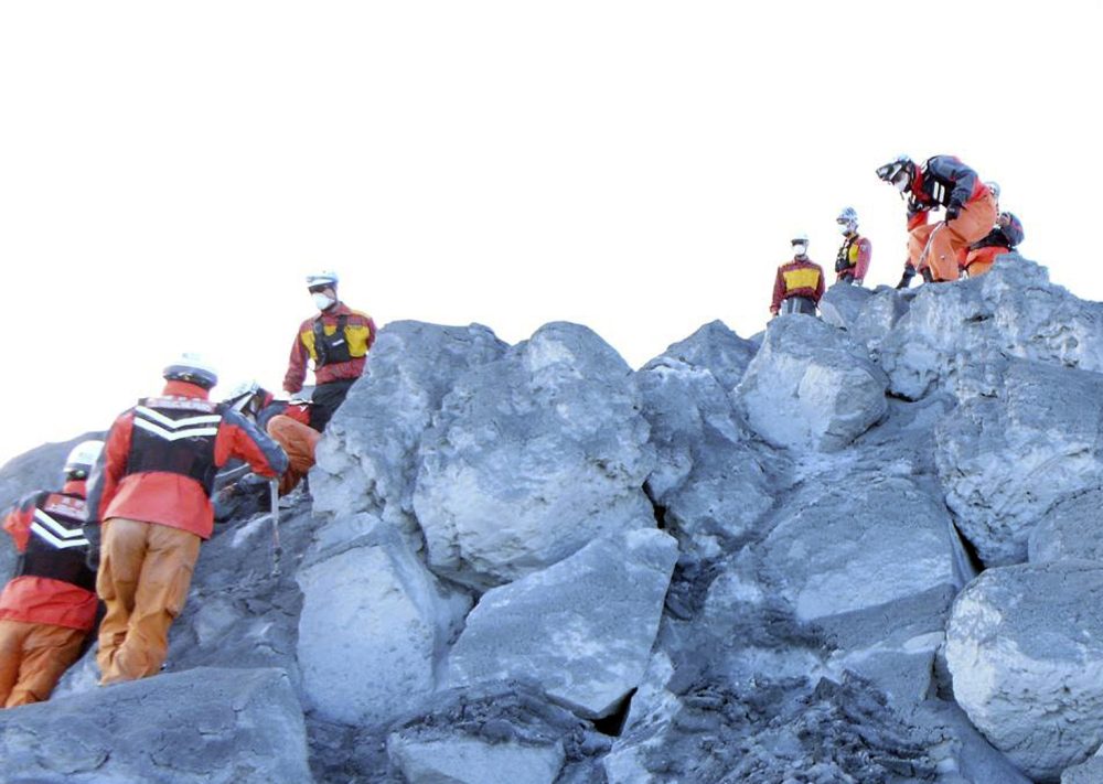 Nagoya City firefighters search for hikers Sunday near the summit of Mount Ontake in Japan.