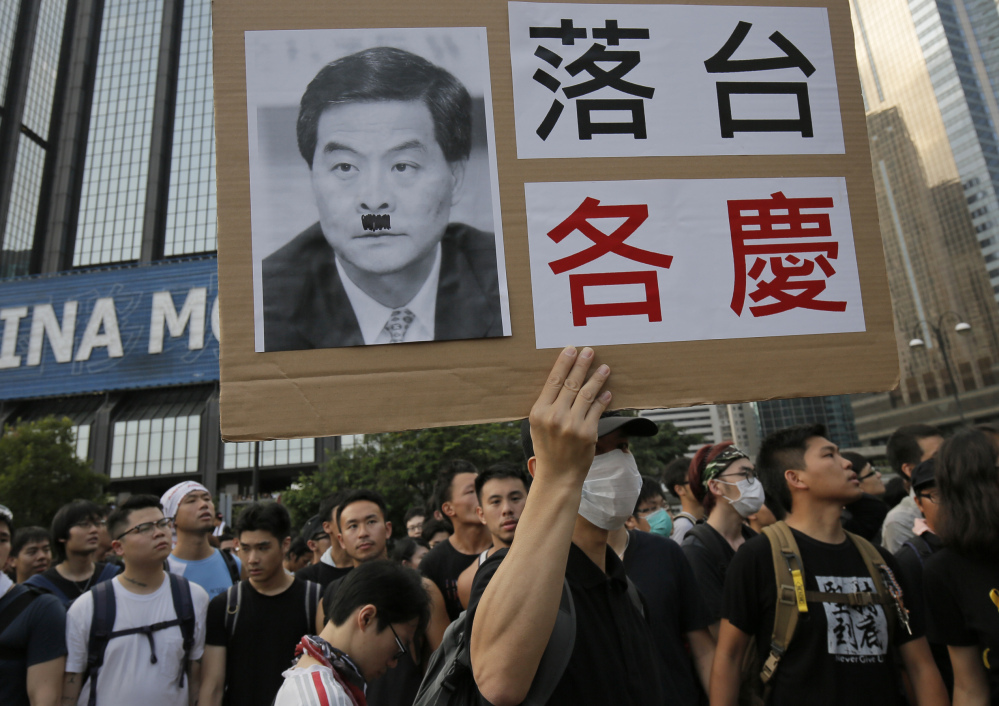 A pro-democracy protester raises a placard with a defaced photo of Hong Kong's Chief Executive Leung Chun-ying outside a flag-raising ceremony Wednesday.