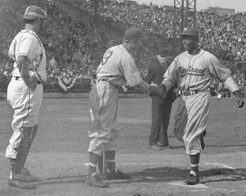 Jackie Robinson, who broke baseball's color barrier, is congratulated by teammate George Shuba after hitting a home run in his first minor league game in 1946.