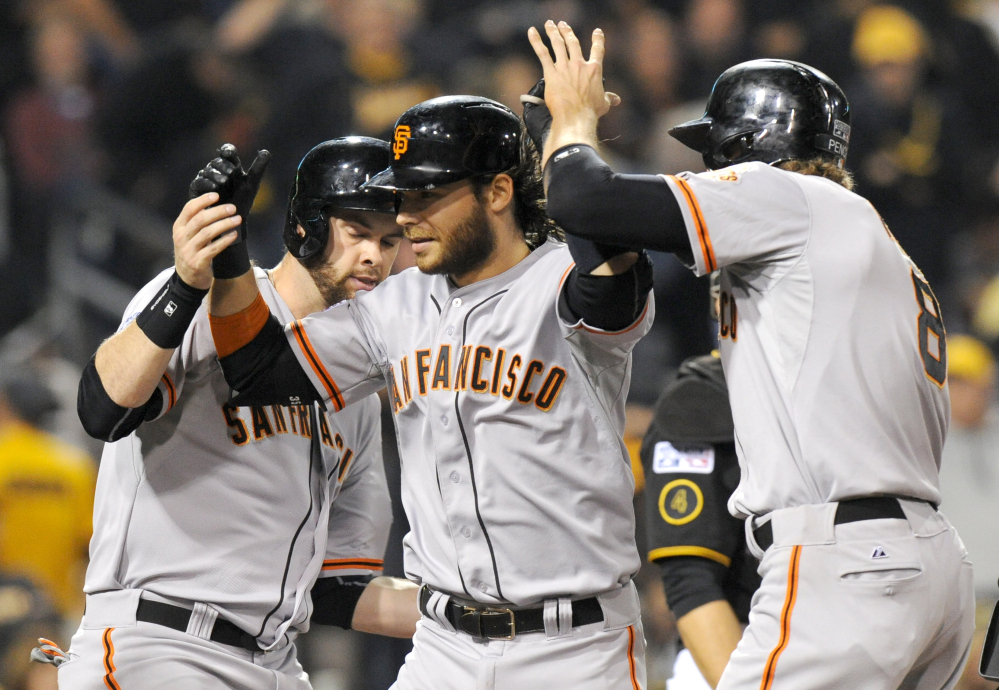 San Francisco Giants shortstop Brandon Crawford, center, is greeted by teammates Brandon Belt, left, and Hunter Pence, right, after hitting a grand slam against the Pittsburgh Pirates in the fourth inning of the NL wild-card playoff game Wednesday in Pittsburgh.