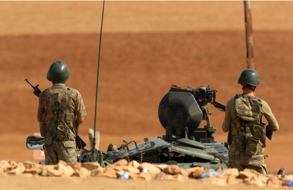 Turkish soldiers stand on a hilltop overlooking the fighting positions between Syrian Kurds and Islamic State militants west of Kobane in Syria, near Suruc, Turkey, on Thursday.