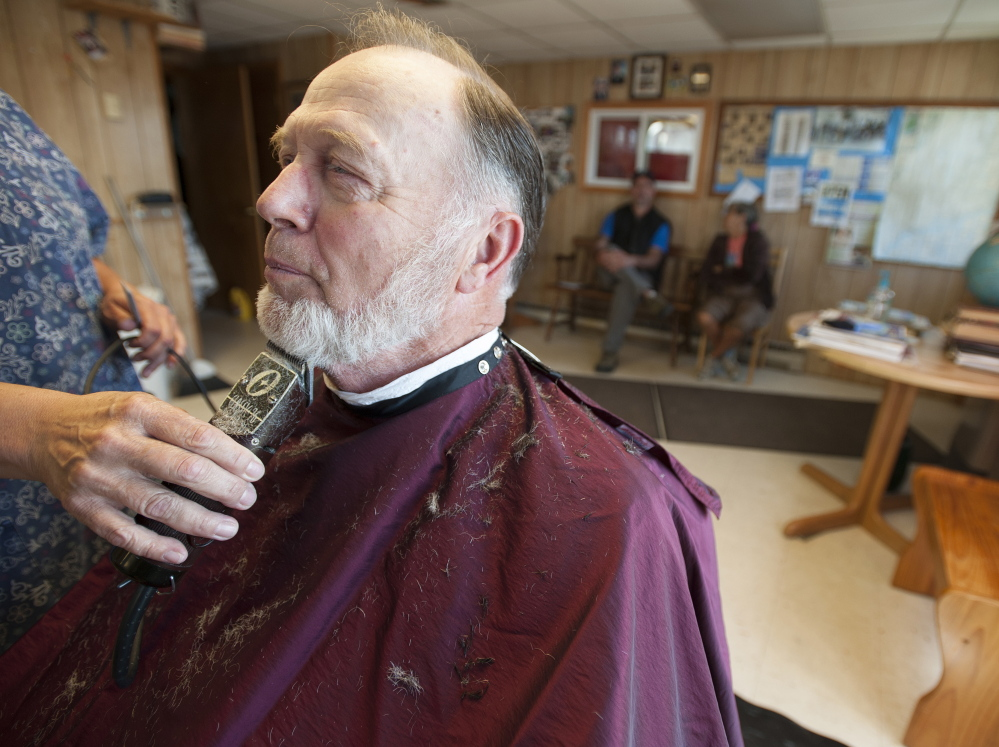 """n Barber Frank Dunbar, a town councilor who has run a barber shop on Main Street in Bucksport for more than 50 years, says, """"We've been living in (the mill's) shadow all these years."""""""