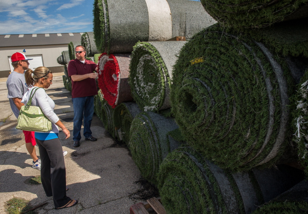 Jerry Kessler, center, offers AstroTurf from a high school in Chicago to Brian Zirkle and Michelle Anderson, who plan to open a sports training facility. The couple didn't buy on the spot but said they would return.