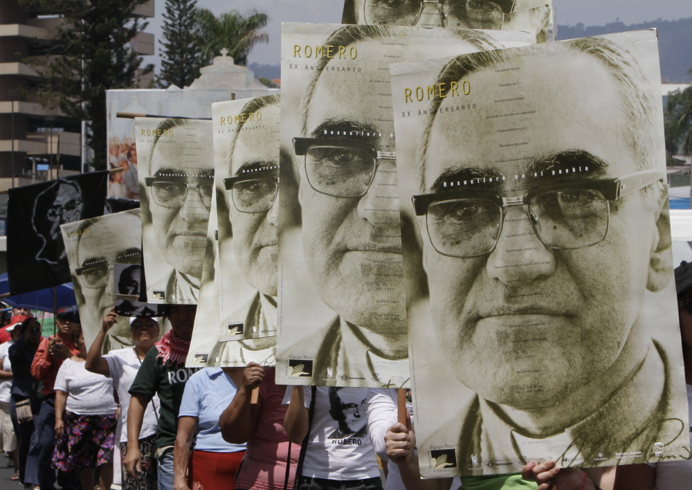 Marchers carry portraits of slain Archbishop Oscar Arnulfo Romero in San Salvador, El Salvador, in 2011. Pope Francis is pushing ahead for Romero's sainthood.