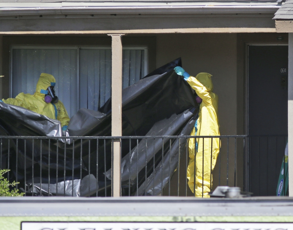 A hazardous-materials crew prepares to hang black plastic Friday outside an apartment in Dallas where an Ebola patient who traveled from Liberia stayed last week.