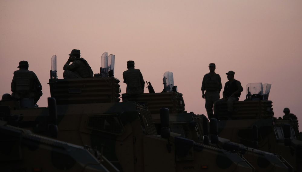 Turkish soldiers are silhouetted as they stand on top of armored vehicles on the Turkish-Syrian border Friday.