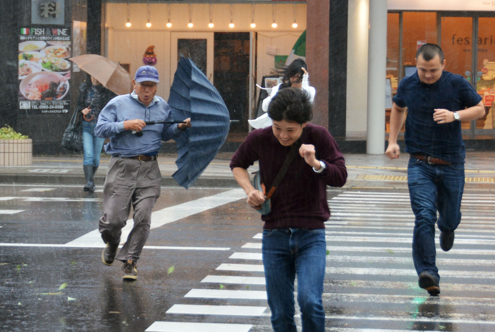 Pedestrians struggle to cross a street in Miyazaki, southern Japan, in heavy rain and strong winds caused by a powerful typhoon approaching to Japan Sunday.
