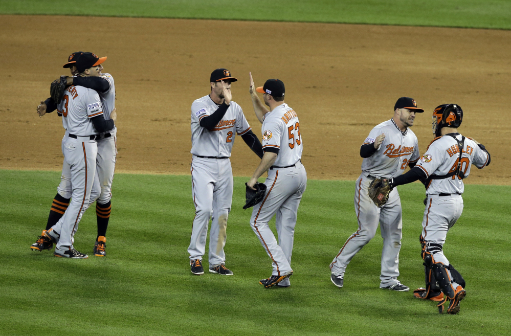 Baltimore Orioles players celebrate after defeating the Detroit Tigers, 2-1 in Game 3 of baseball's AL Division Series Sunday, in Detroit. Baltimore won the series 3-0.