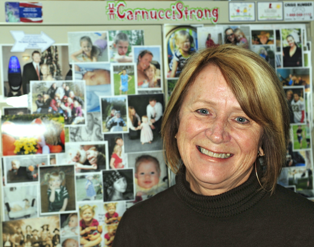 Charle Clark displays a Carnucci Strong sign with family photos in her office at the Winthrop police station.