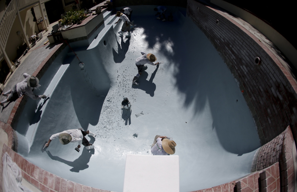 Workers replace the plaster in a swimming pool in Santa Ana, Calif. Amid California's drought, new rules range from requiring a pool cover to prevent evaporation to banning residents from draining and refilling older pools that need repairs.