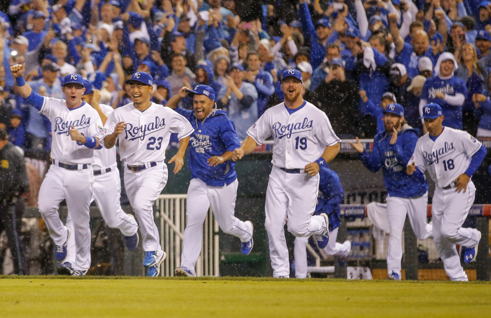 Kansas City Royals players erupt from the dugout following Game 3 of the American League Division Series in Kansas City, Mo., on Sunday. The Royals defeated the Los Angeles Angels 8-3 to sweep the series.