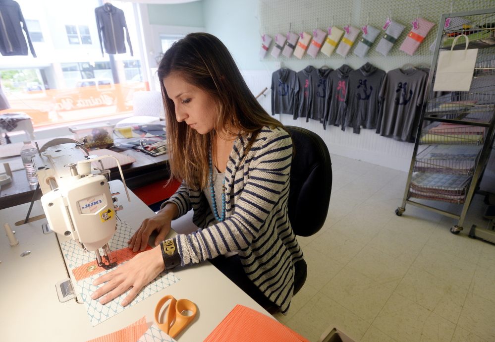 Alaina Harris, 26, owner of Alaina Marie, sews one of her items made from bait bag material in her South Portland studio and store on Thursday.