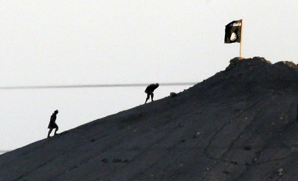 Islamic State militants are seen after placing their group's flag on a hilltop at the eastern side of the town of Kobani, Syria, where fighting with Syrian Kurds intensified Monday.