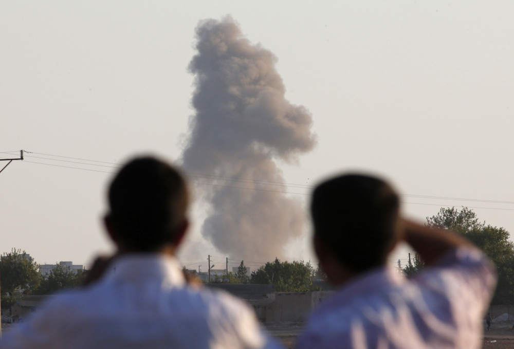 Turkish Kurds on the outskirts of Suruc, on the Turkey-Syria border, watch smoke rise after an airstrike in Kobani, Syria, where the fighting between the Islamic State group and Kurdish forces intensified Tuesday.