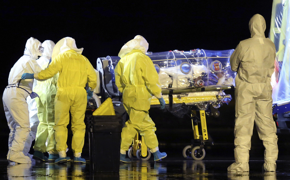 Aid workers and doctors transfer Manuel Garcia Viejo, a Spanish priest who was diagnosed with the Ebola virus while working in Sierra Leone, from a military plane to an ambulance as he leaves the Torrejon de Ardoz military airbase, near Madrid, Spain.