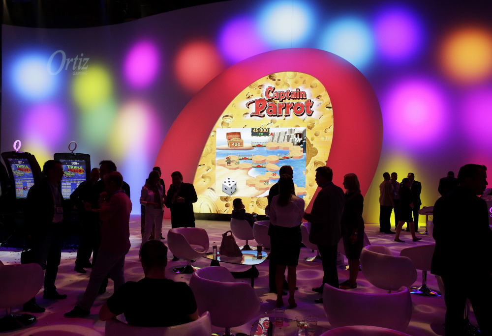 People visit the Ortiz Gaming booth during the Global Gaming Expo in Las Vegas this month. Slot machine manufacturers are updating games with more current themes and features such as touch screens to attract younger dollars.