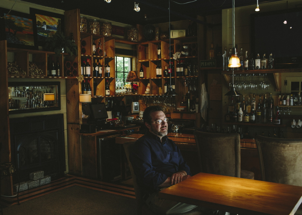 Owner Matt Mattingly sits in the wine bar at the PineCrest Inn Bed and Breakfast in Gorham as he tests software for Davo Technologies that eliminates the need for businesses to crunch their sales-tax numbers every month.